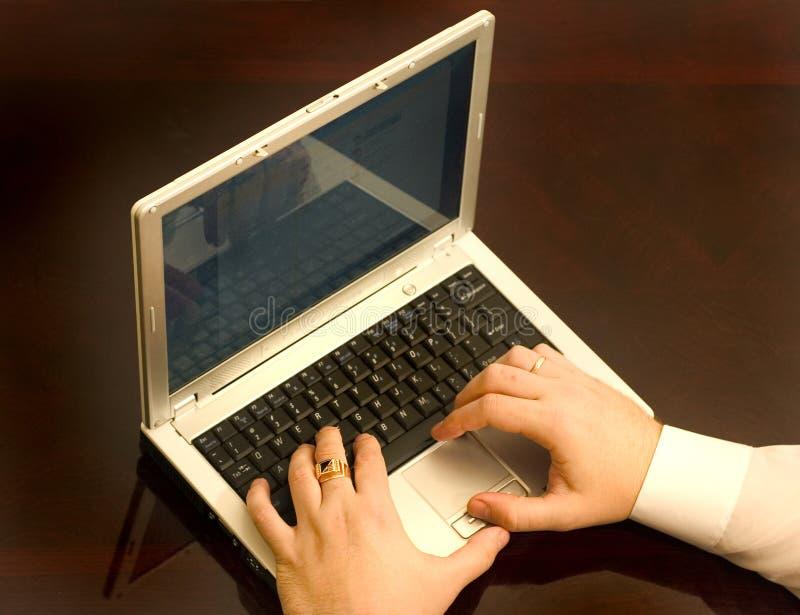 Homme travaillant sur l'ordinateur portatif photographie stock libre de droits