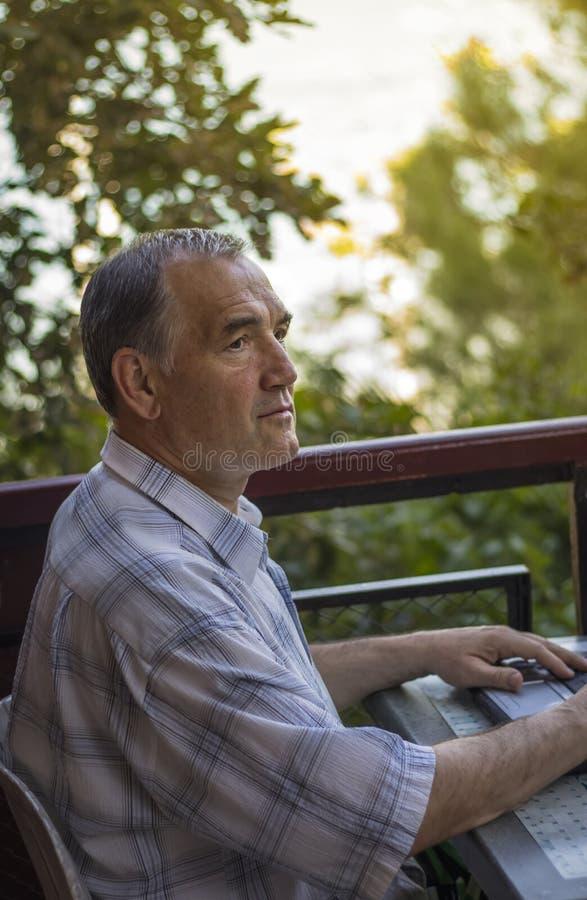 Homme travaillant sur son ordinateur portable sur le balcon photographie stock