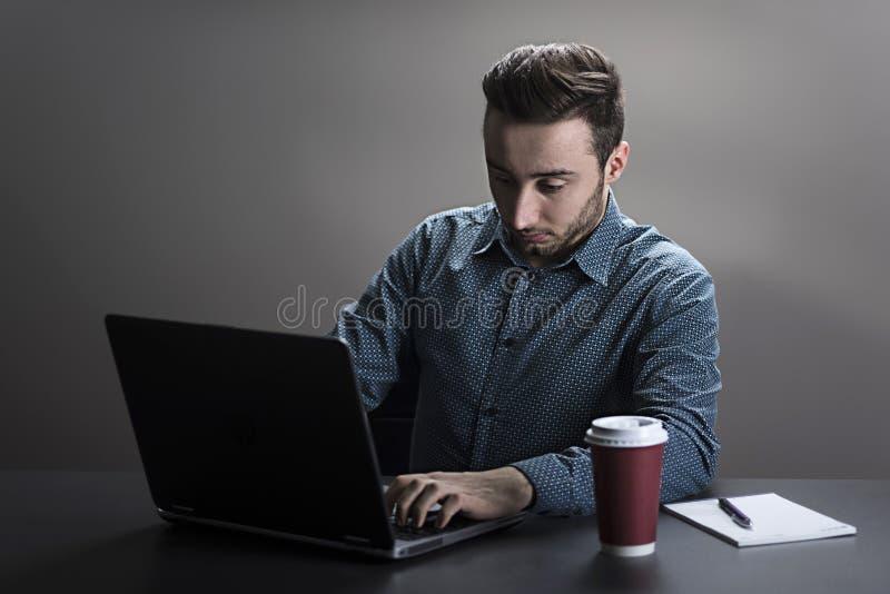 Homme travaillant sur un ordinateur portatif photo stock