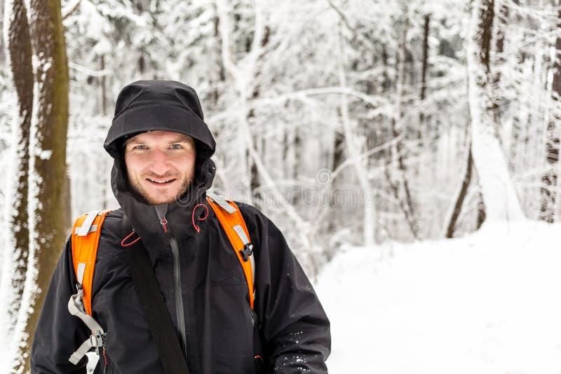 Homme trimardant dans la forêt d'hiver image stock