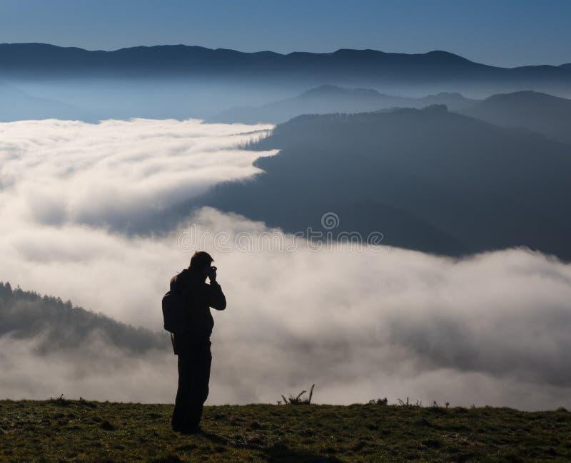Homme trimardant en montagnes photographiant et appréciant le temps beau en parc naturel de harriak d'aiako photos stock