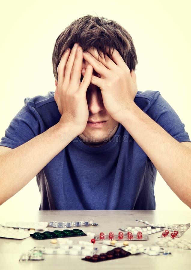 Homme triste avec pilules image stock