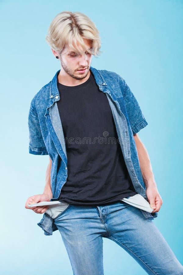Homme triste bouleversé montrant les poches vides photos stock