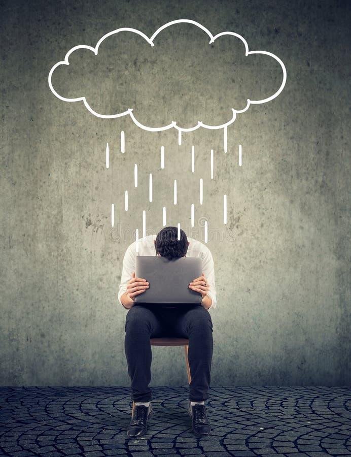 Homme triste d'affaires s'asseyant sur une chaise avec l'ordinateur portable regardant vers le bas avec un nuage de pluie ci-dess photos libres de droits