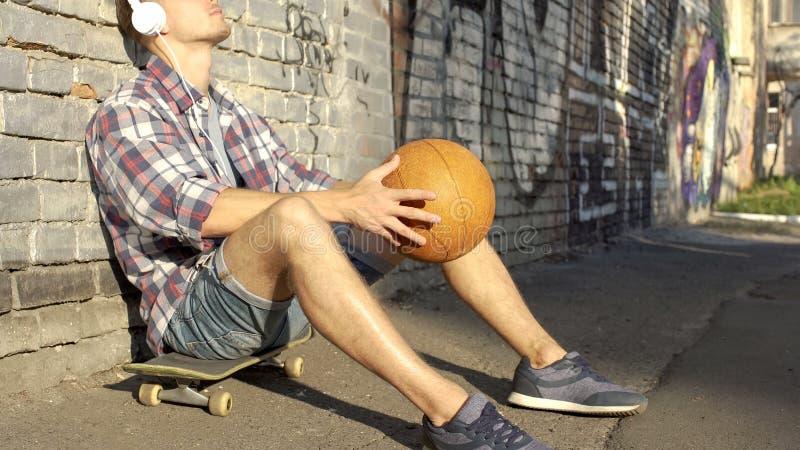 Homme triste dans des écouteurs se reposant sur la planche à roulettes, pensant à la vie, tenant la boule images stock