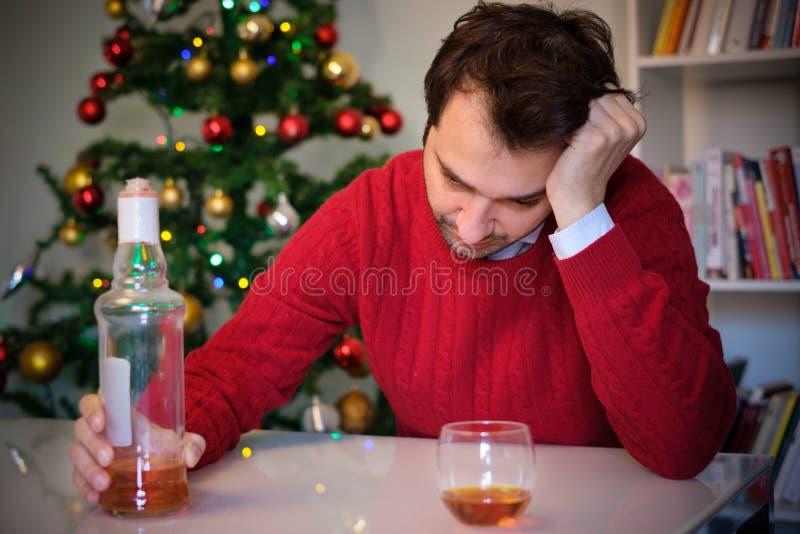 Homme triste dans la solitude pour l'abus d'alcool tout seulement pendant le Noël image stock