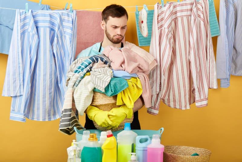 Homme triste malheureux sérieux faisant les travaux domestiques images stock