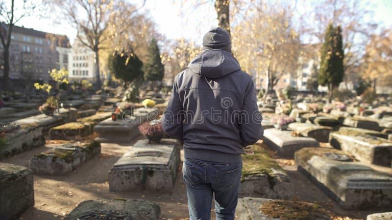 Homme triste marchant sur le cimetière antique, parent de visite, commémorant des ancêtres photos libres de droits