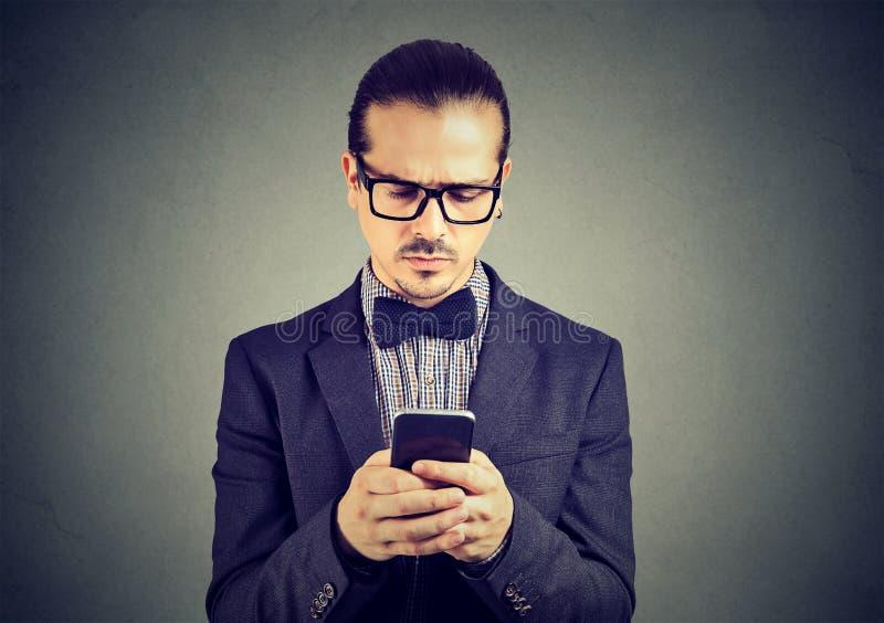 Homme triste préoccupé pensant quoi répondre au message textuel reçu au téléphone portable photographie stock libre de droits