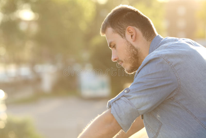 Homme triste regardant vers le bas dans un balcon photographie stock libre de droits