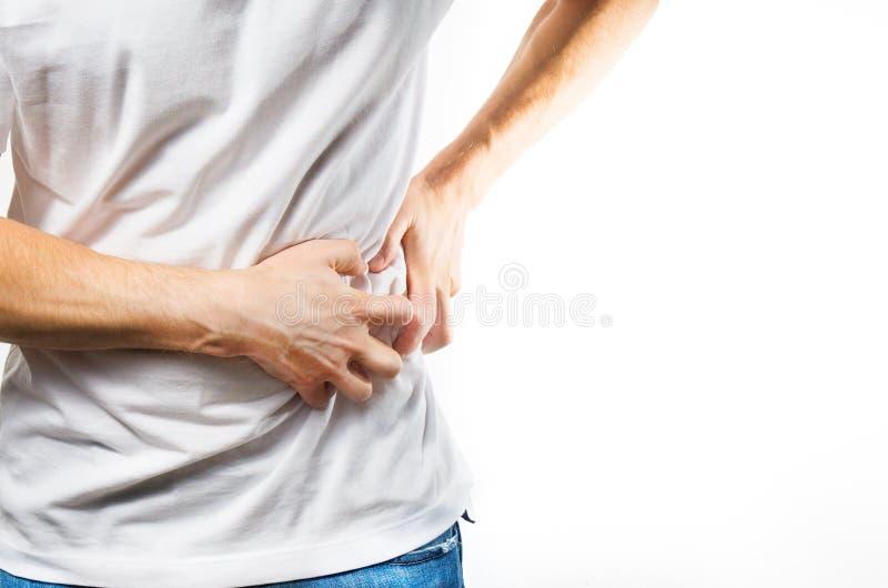 Homme, type dans un T-shirt blanc sur les mains blanches d'une prise de fond sur son estomac, douleur de foie, pancréas, problème photos libres de droits