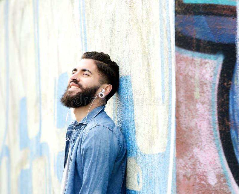 Homme urbain écoutant la musique sur des écouteurs photographie stock libre de droits