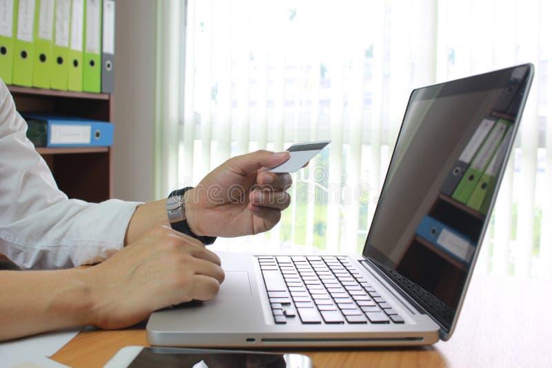 Homme utilisant l'ordinateur portable et les mains tenant la carte de crédit, concept en ligne de paiement photo stock