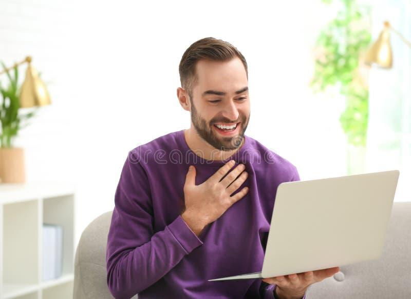 Homme utilisant l'ordinateur portable pour la causerie visuelle photographie stock libre de droits