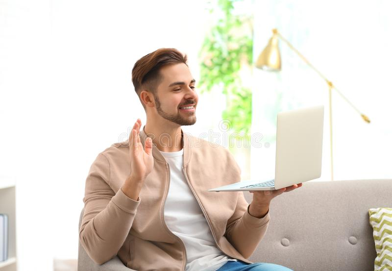 Homme utilisant l'ordinateur portable pour la causerie visuelle image stock