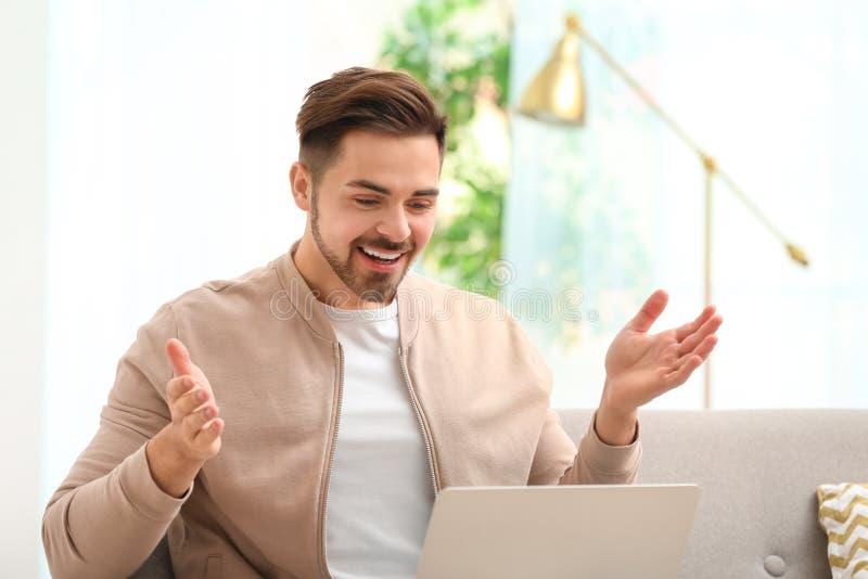 Homme utilisant l'ordinateur portable pour la causerie visuelle images stock