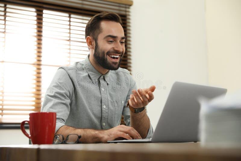 Homme utilisant la causerie visuelle sur l'ordinateur portable photos libres de droits