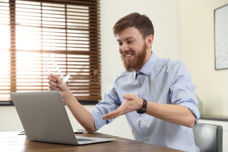 Homme utilisant la causerie visuelle sur l'ordinateur portable image libre de droits