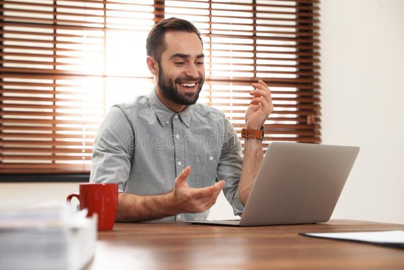 Homme utilisant la causerie visuelle sur l'ordinateur portable photographie stock libre de droits