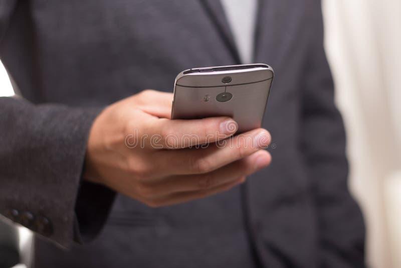 Homme utilisant la veste noire de costume tenant Gray Htc Android Smartphone photos libres de droits