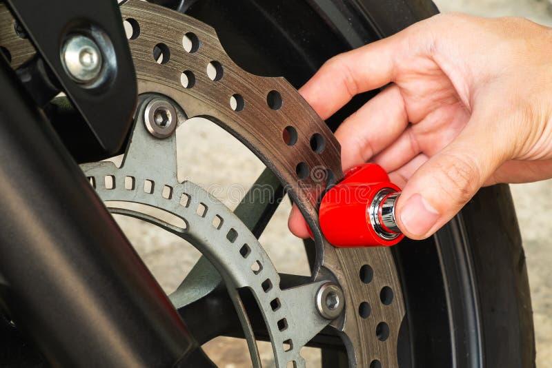 Homme utilisant le collier de frein de disque de moto pour fixer son voleur de forme de moto image stock