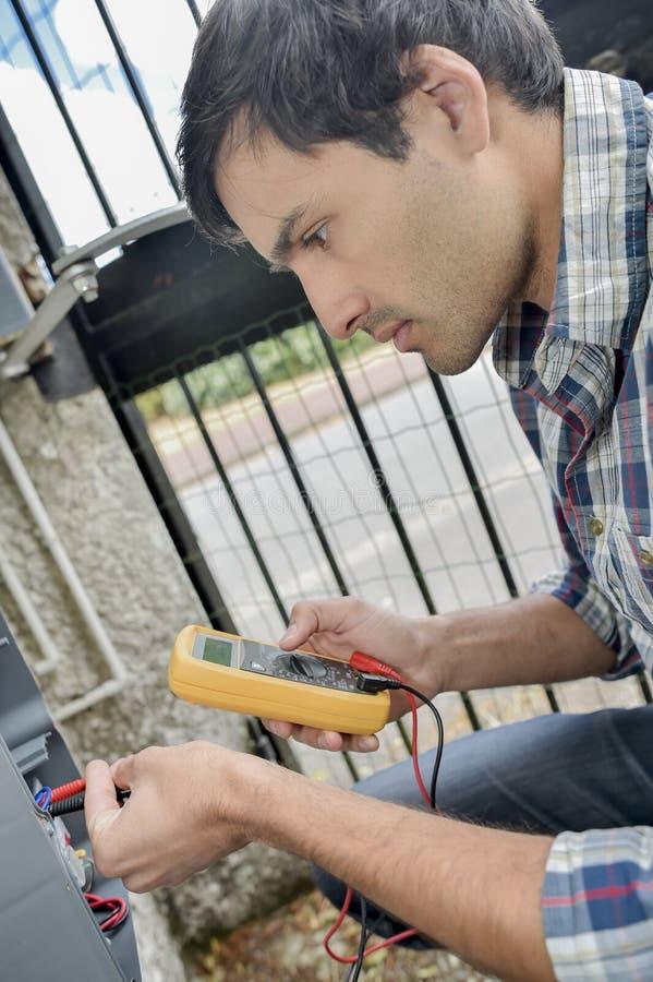 Homme utilisant le multimètre sur la boîte électrique extérieure photos stock