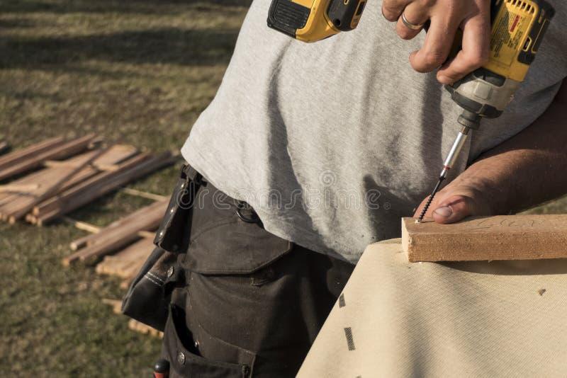 Homme utilisant le scredriver électrique pour attacher des éléments de construction photos libres de droits