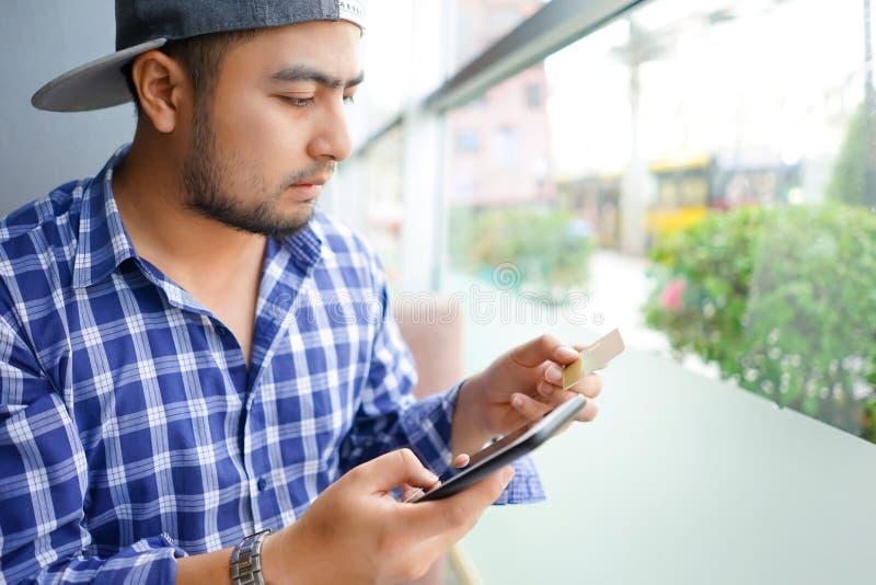 Homme utilisant le smartphone mobile et carte de crédit pour des achats en ligne dans le café Homme d'affaires occasionnel s'asse photographie stock