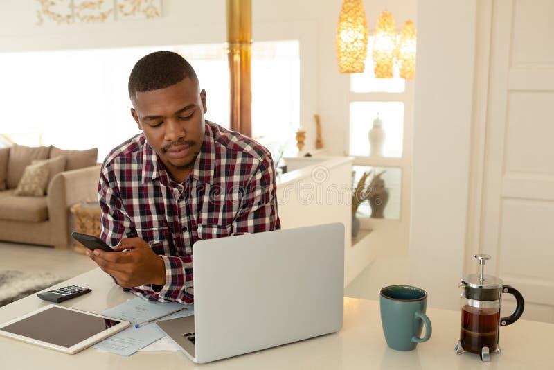 Homme utilisant le téléphone portable et l'ordinateur portable à la table dans une maison confortable photo stock