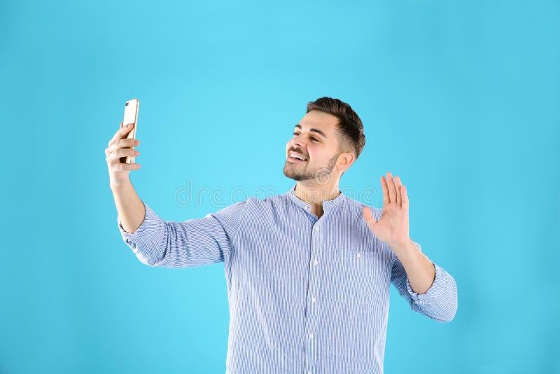 Homme utilisant le téléphone portable pour la causerie visuelle image stock