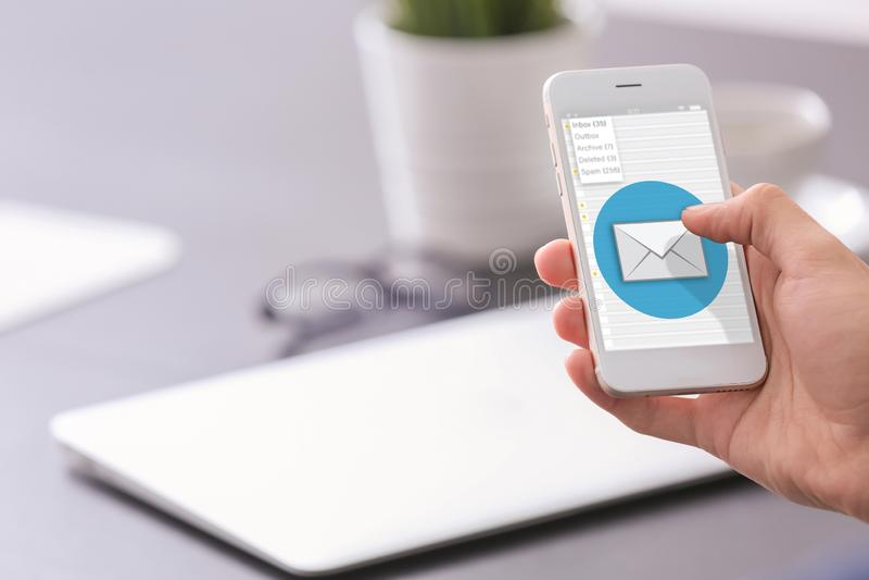 Homme utilisant le téléphone portable pour vérifier un email sur le lieu de travail, plan rapproché photos libres de droits