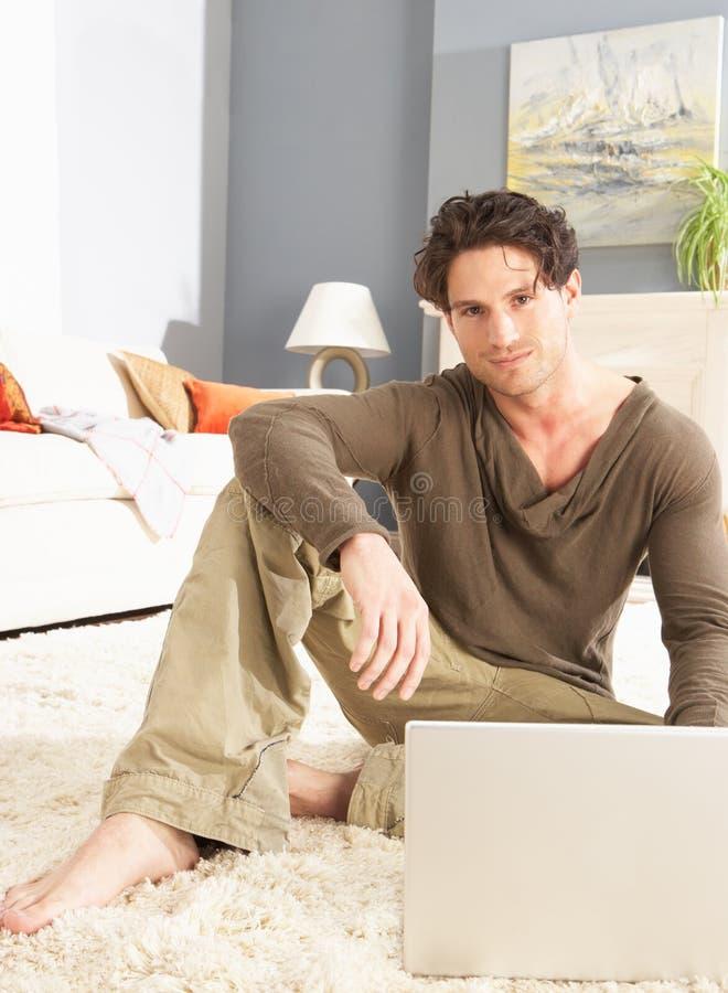 Homme utilisant se reposer de détente d'ordinateur portatif sur la couverture à la maison photographie stock libre de droits