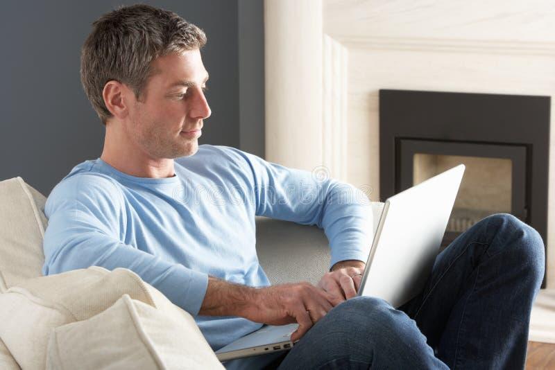 Homme utilisant se reposer de détente d'ordinateur portatif sur le sofa à la maison photographie stock libre de droits