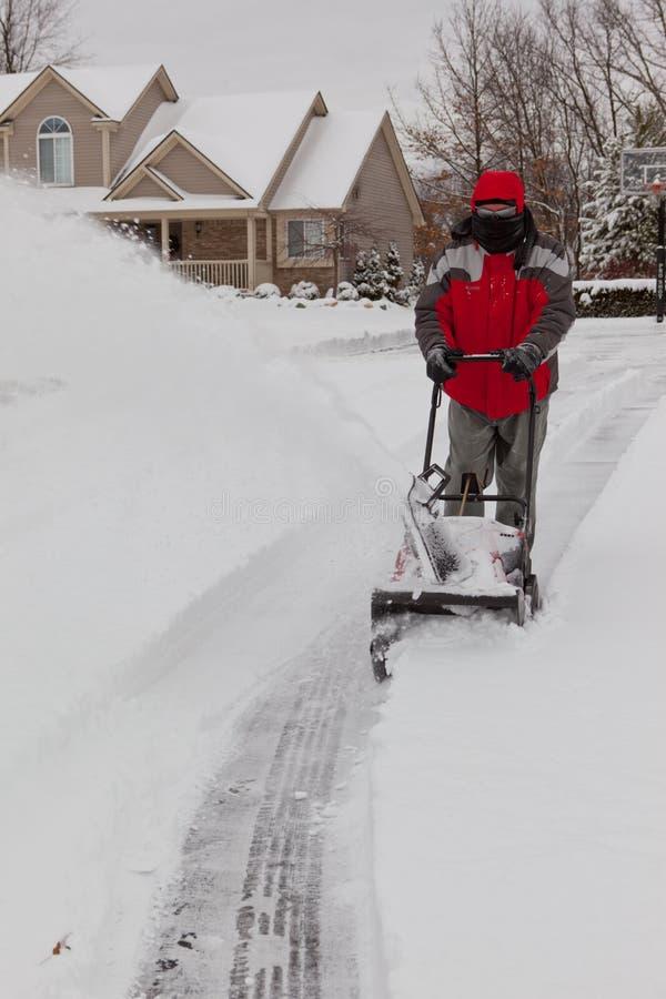Homme utilisant un ventilateur de neige photographie stock libre de droits