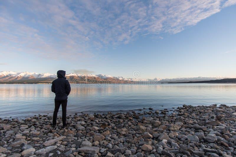 Homme utilisant une veste bleue se tenant sur des roches regardant le cuisinier de Mt, Nouvelle-Zélande photographie stock