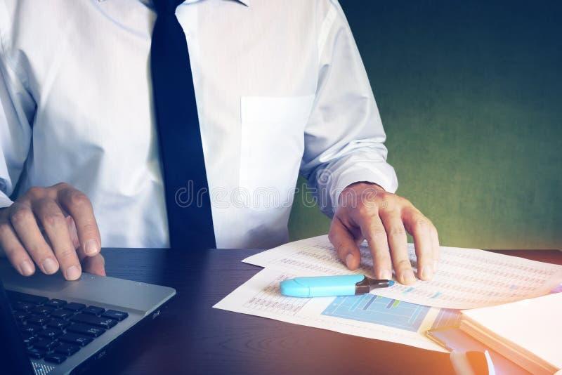 Homme vérifiant dans des données financières d'ordinateur portable photos stock