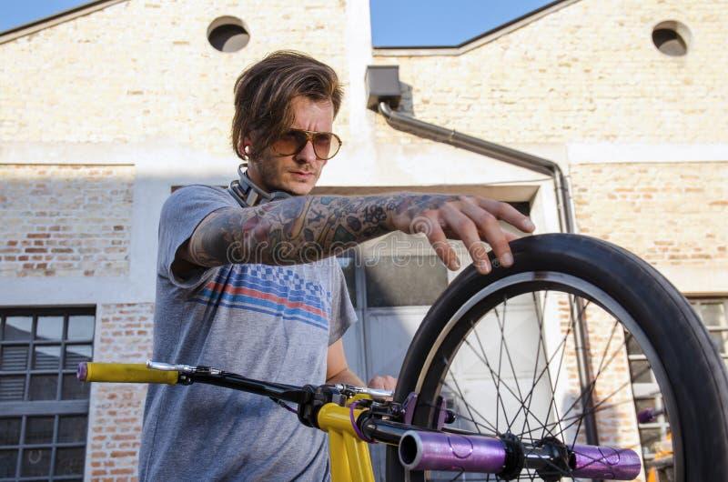 Homme vérifiant des pneus sur son vélo de bmx image stock