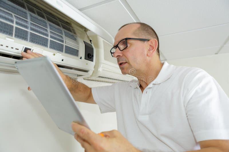 Homme vérifiant le manuel de climatisation tout en l'employant photographie stock