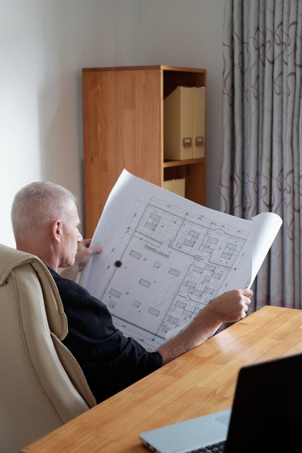 Homme vérifiant le plan de construction photos stock