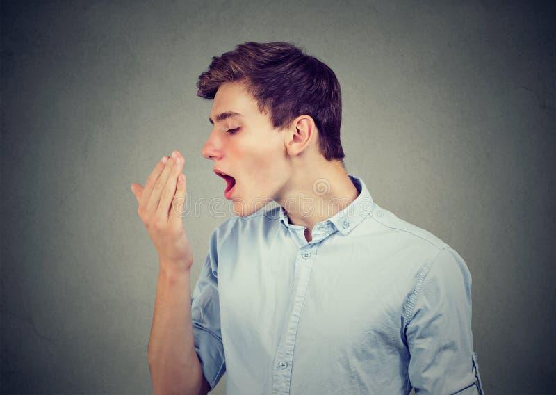 Homme vérifiant son souffle avec la main image libre de droits