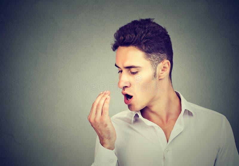 Homme vérifiant son souffle avec la main images stock