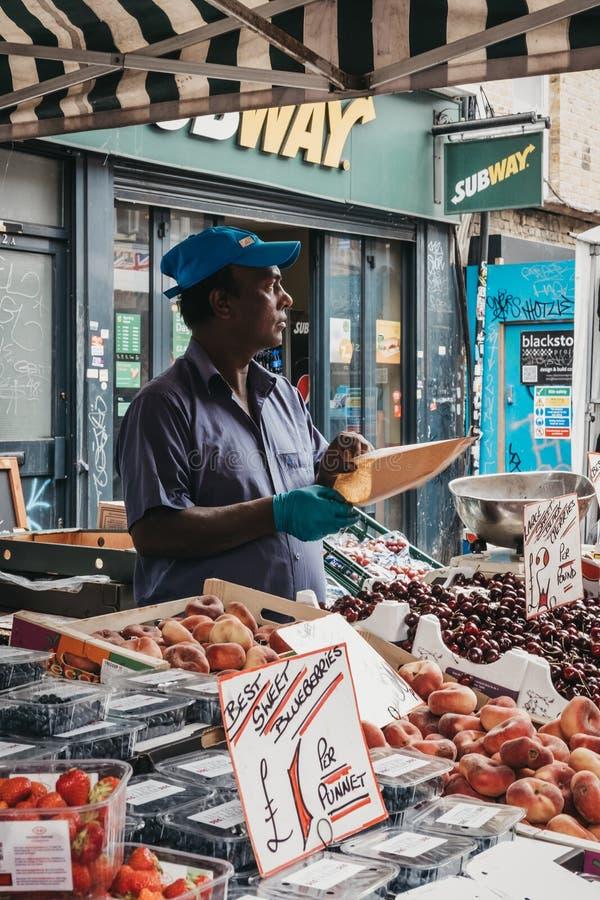 Homme vendant le fruit frais dans la ruelle de brique, Londres, R-U images libres de droits