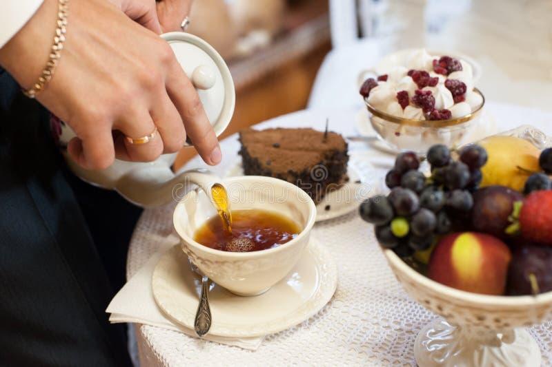 Homme versant le thé anglais dans la tasse photo stock