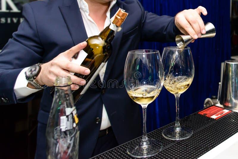 Homme versant le vin rouge dans un verre image libre de droits
