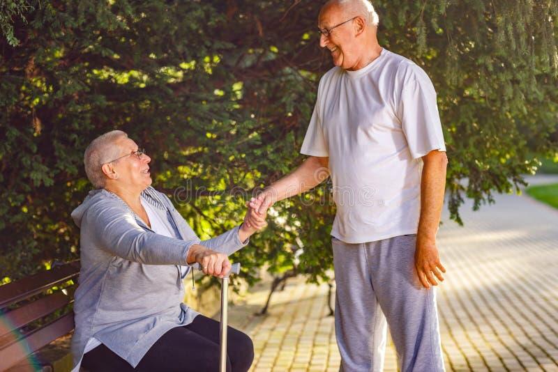 Homme vieillissant soutenant l'épouse malade en parc image stock