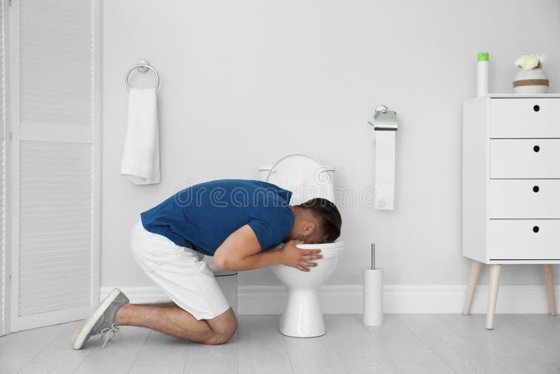 Homme vomissant dans la cuvette des toilettes à la maison photos libres de droits