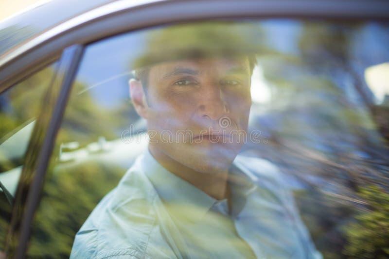Homme vu par la fenêtre de voiture image stock