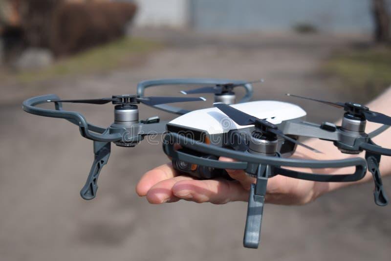 Hommel in de handen van de persoon Nieuwe technologie in aerofoto het schieten Proeflanceringen quadrupter van zijn palm stock afbeelding