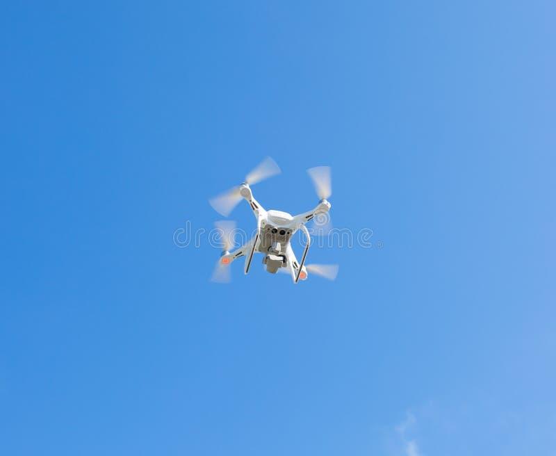 Hommel, die tegen de blauwe hemel de vliegen quadrocopter fpv vliegt camera rc controlemechanisme stock foto