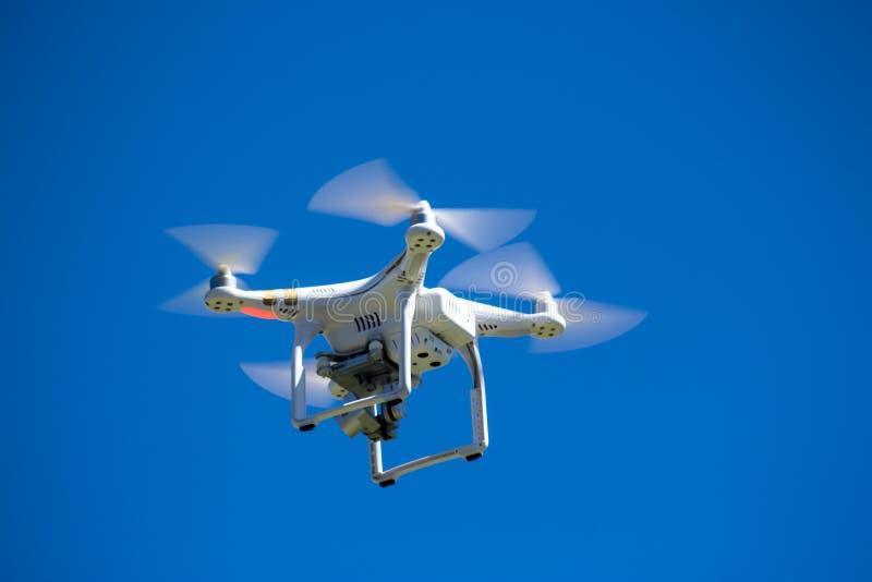 Hommel of onbemand luchtvoertuig tijdens de vlucht tegen blauwe hemel stock afbeeldingen